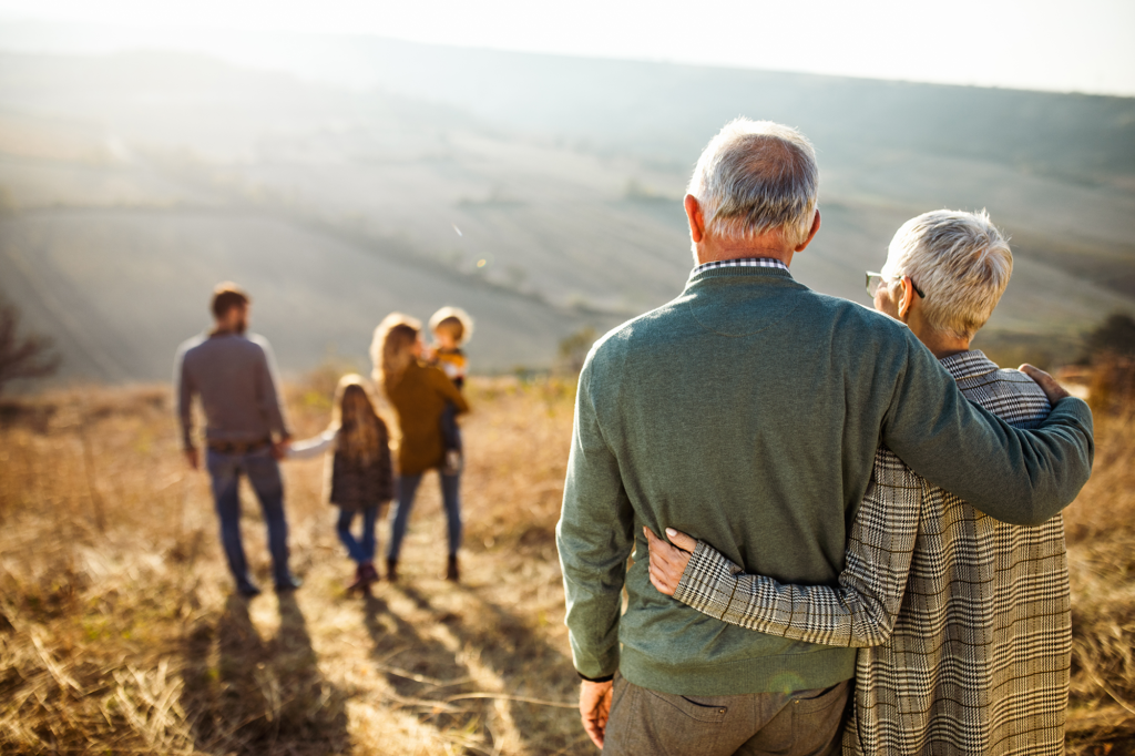 Senior couple watching family on hill