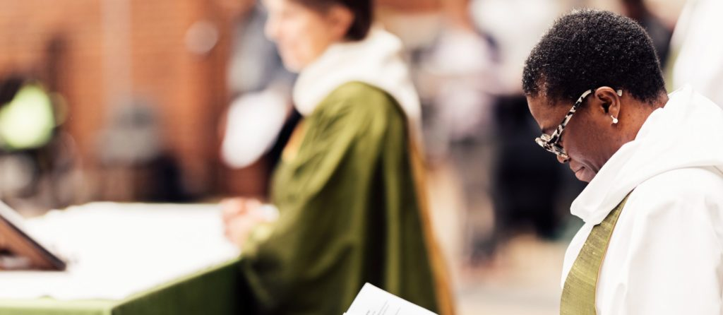 two female priests in a church service